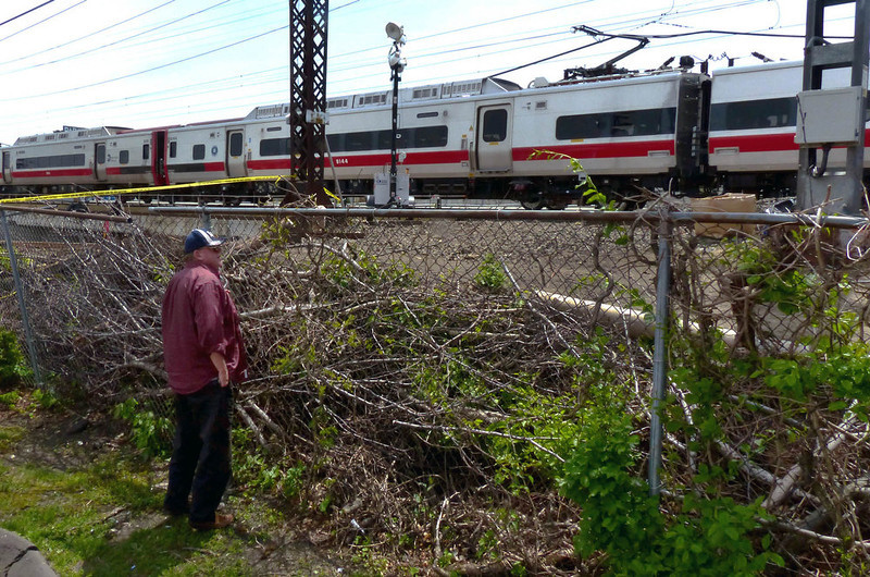 . An onlooker looks at the Metro-North commuter trains involved in the train derailment, Saturday, May 18, 2013 in Bridgeport, Conn. Officials described a devastating scene of shattered cars and other damage where two trains packed with rush-hour commuters collided in Connecticut, saying Saturday it\'s fortunate that no one was killed and that there weren\'t even more injuries. (AP Photo/The Connecticut Post, Christian Abraham)