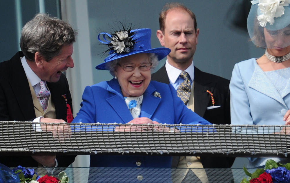 Description of . Britain's Queen Elizabeth II (C) standing next to Prince Edward, Earl of Wessex (2R) smiles from the royal balcony as she looks down on the winning horse in the Derby race on Derby Day, the second day of the Epsom Derby horse racing festival, at Epsom in Surrey, southern England, on June 2, 2012 the first official day of Britain's Queen Elizabeth II's Diamond Jubilee celebrations.     AFP PHOTO / CARL COURT/AFP/Getty Images