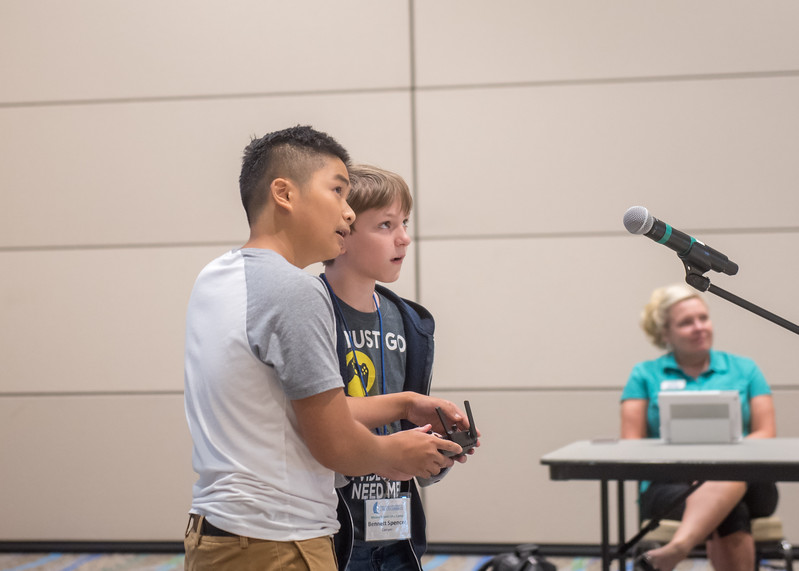 Student Vincent Nguyen instructs UAS camp attendee Bennett Spencer on how to fly a quadcoptor.