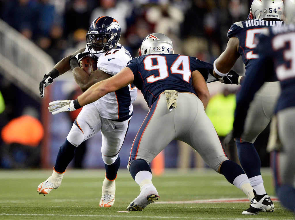 . Denver Broncos running back Knowshon Moreno (27) picks up a big gain as before he is brought down by New England Patriots defensive tackle Chris Jones (94)  during the first quarter against the Denver Broncos November 24, 2013 at Gillette Stadium.  (Photo by John Leyba/The Denver Post)