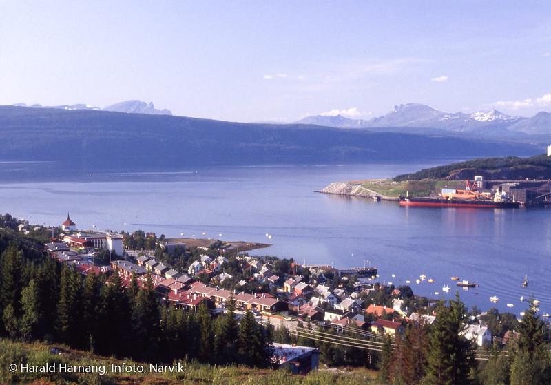 Ankenes fotografert fra slalombakken. Kirka til venstre. Nærmest hysrekkene i Brattliveien. Malmskip laster ved kai 5. Båter på sjøen. Antonsenkaia ved torget.