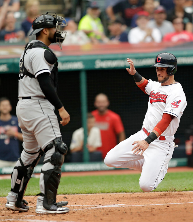 . Cleveland Indians\' Yan Gomes, right, slides safely into home plate as Chicago White Sox catcher Omar Narvaez watches in the fourth inning of a baseball game, Wednesday, June 20, 2018, in Cleveland. Gomes scored on a single by Rajai Davis. (AP Photo/Tony Dejak)