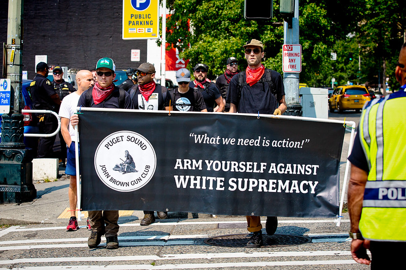 """Members of the Puget Sound John Brown Gun Club cross the street carrying a banner reading, """"'What we need is action!' ARM YOURSELF AGAINST WHITE SUPREMACY."""""""
