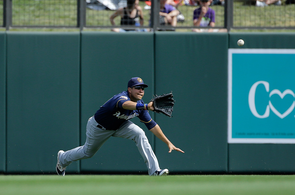 . Milwaukee Brewers center fielder Ramon Flores catches a fly ball hit by Colorado Rockies\' Nolan Arenado during the first inning of a spring training baseball game in Scottsdale, Ariz., Tuesday, March 22, 2016. (AP Photo/Jeff Chiu)