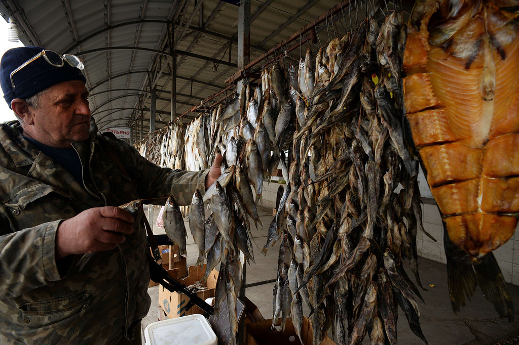 """. A member of armed pro-Russian forces chooses fish at a stall near a checkpoint in Chongar, in the border area between Crimea and the Kherson region of Ukraine, on March 14, 2014. Russia and the West have \""""no common vision\"""" on Ukraine, Foreign Minister Sergei Lavrov said today after talks aimed at defusing the crisis.  VASILY MAXIMOV/AFP/Getty Images"""