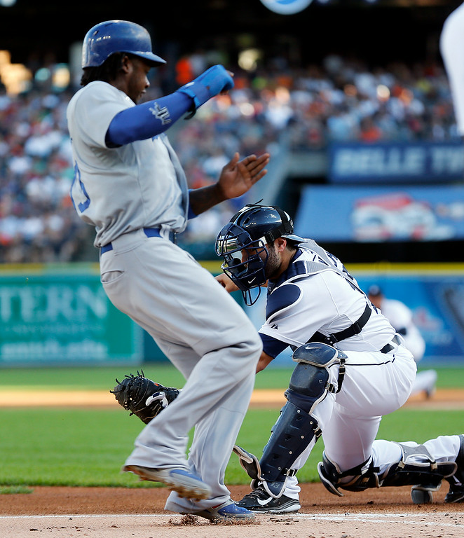 . Los Angeles Dodgers\' Hanley Ramirez runs past the tag of Detroit Tigers catcher Alex Avila to score in the first inning of a baseball game in Detroit, Tuesday, July 8, 2014. (AP Photo/Paul Sancya)