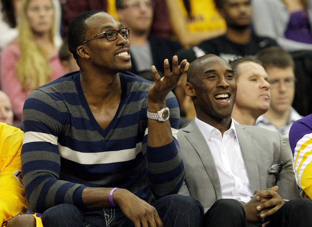 . Los Angeles Lakers center Dwight Howard, left, sitting out the game after back surgery, and guard Kobe Bryant, with a strained right shoulder, spent the game on the bench in an NBA basketball game against the Portland Trail Blazers in Ontario, Calif., Wednesday, Oct. 10, 2012. Portland won, 93-75. (AP Photo/Reed Saxon)