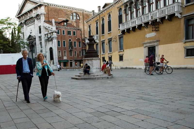 Senior couple walking the dog on Campo San Stefano, Venice, Italy