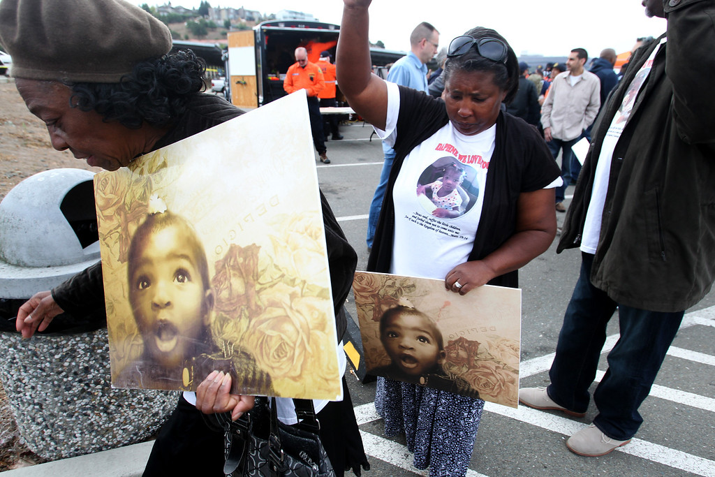 . Family members of missing 22-month-old Daphne Webb carry photo enlargements of the child as Oakland police, along with Alameda County Sheriff and Santa Clara County Sheriff volunteer rescue teams and FBI agencies, begin the search for the missing child near Merritt College in Oakland, Calif., on Saturday, Aug. 24, 2013. (Ray Chavez/Bay Area News Group)