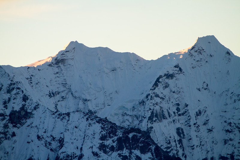 Morning light just barely illuminates the flanks of peaks in the Himalayas of Nepal