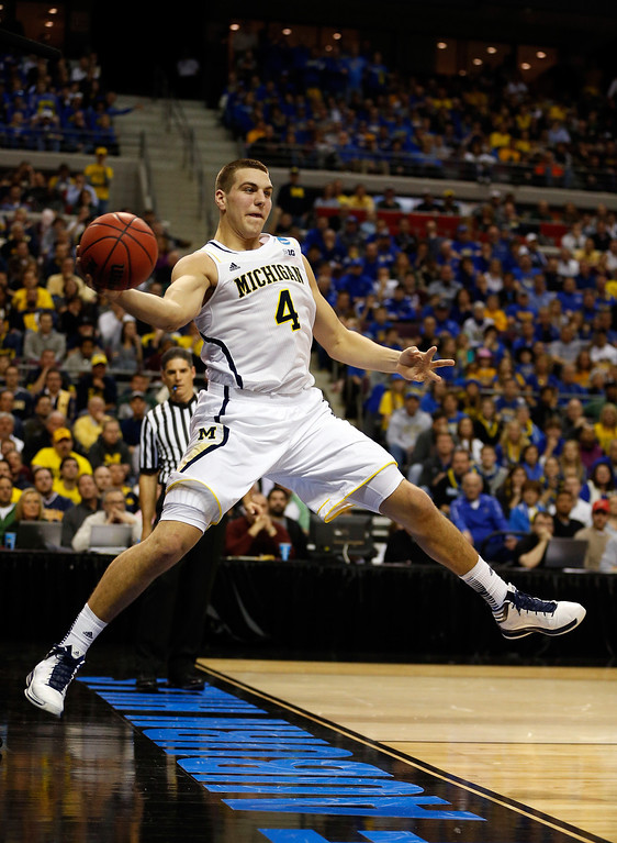 . Mitch McGary #4 of the Michigan Wolverines attempts to pass the ball before going out of bounds against the South Dakota State Jackrabbits during the second round of the 2013 NCAA Men\'s Basketball Tournament at at The Palace of Auburn Hills on March 21, 2013 in Auburn Hills, Michigan.  (Photo by Gregory Shamus/Getty Images)