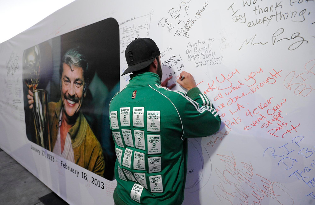 . Adam Lowell drove his Celtics jacket all the way from San Diego to attend the game tonight. Here he signes a poster of Jerry Buss. The Lakers posted large banners around LA Live and Staples Center with a photo of Jerry Buss and plenty of room for fans to write their best wishes. Los Angeles, CA 2/20/2013(John McCoy/Staff Photographer)