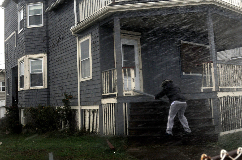 . A woman pulls a piece of porch off her home as water crashes over her on Winthrop Shore Drive as heavy winds and waves rip the region from Hurricane Sandy on October 29, 2012 in Winthrop, Massachusetts. Hurricane Sandy, which threatens 50 million people in the eastern third of the U.S., is expected to bring days of rain, high winds and possibly heavy snow to a wide area on the U.S. East Coast. (Photo by Darren McCollester/Getty Images)