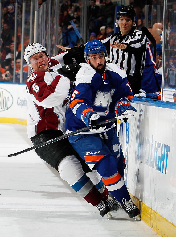 . UNIONDALE, NY - FEBRUARY 08:  Erik Johnson #6 of the Colorado Avalanche checks Cal Clutterbuck #15 of the New York Islanders during the second period of an NHL hockey game at Nassau Veterans Memorial Coliseum on February 8, 2014 in Uniondale, New York.  (Photo by Paul Bereswill/Getty Images)