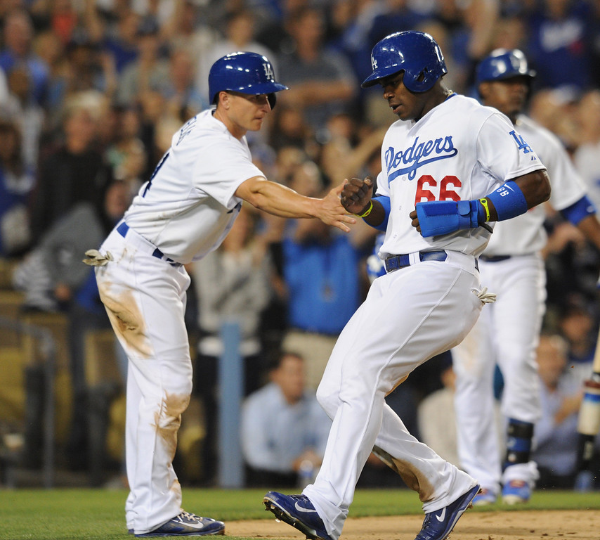 . Mark Ellis reaches out to welcome Yasiel Puig home after A.J. Ellis hit a single to score the two runners in the 6th inning. The Dodgers played the New York Mets in a game at Dodger Stadium in Los Angeles, CA. 8/13/2013(John McCoy/LA Daily News)
