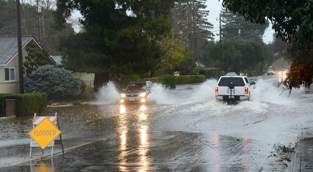 . Motorists drive through flood water on Center Road near Wilson Avenue in Novato, Calif., on Thursday, Dec. 11, 2014. (Alan Dep/Marin Independent Journal)