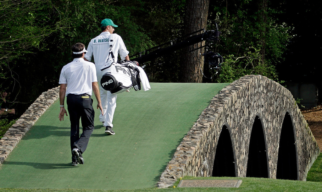 . Bubba Watson walks across the Hogan Bridge with his caddie Ted Scott during the fourth round of the Masters golf tournament Sunday, April 13, 2014, in Augusta, Ga. (AP Photo/Darron Cummings)