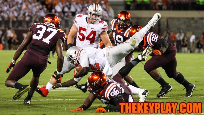 Ohio State quarterback Cardale Jones (12) gets tackled by Corey Marshall (96). (Mark Umansky/TheKeyPlay.com)