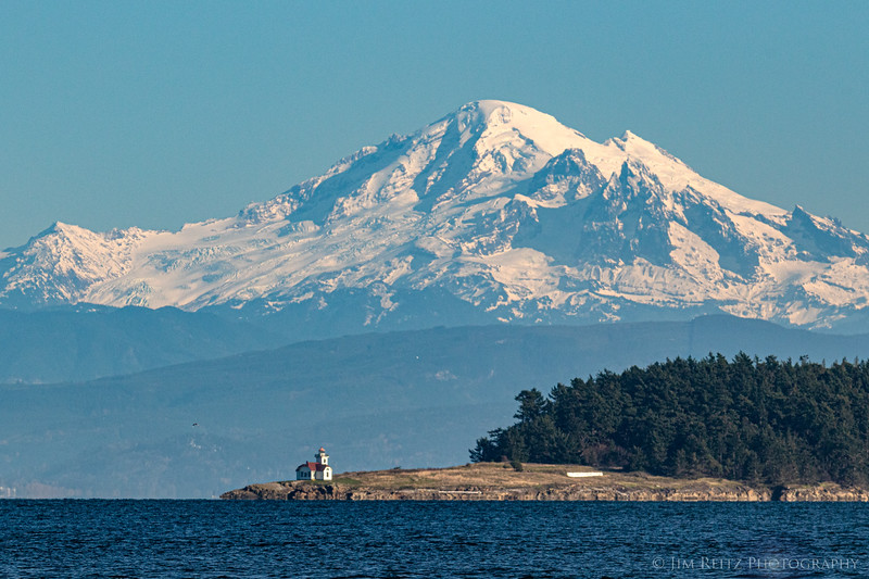Patos Island lighthouse in front of a distant Mount Baker.