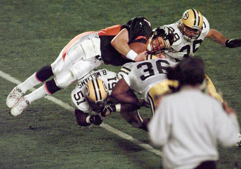 . Denver Broncos quarterback John Elway is flipped by Green Bay Packers\' Brian Williams (51) and Elroy Butler (36) for a first down during Super Bowl XXXII at Qualcomm Stadium in San Diego Sunday, Jan. 25, 1998. (AP Photo/Elaine Thompson)