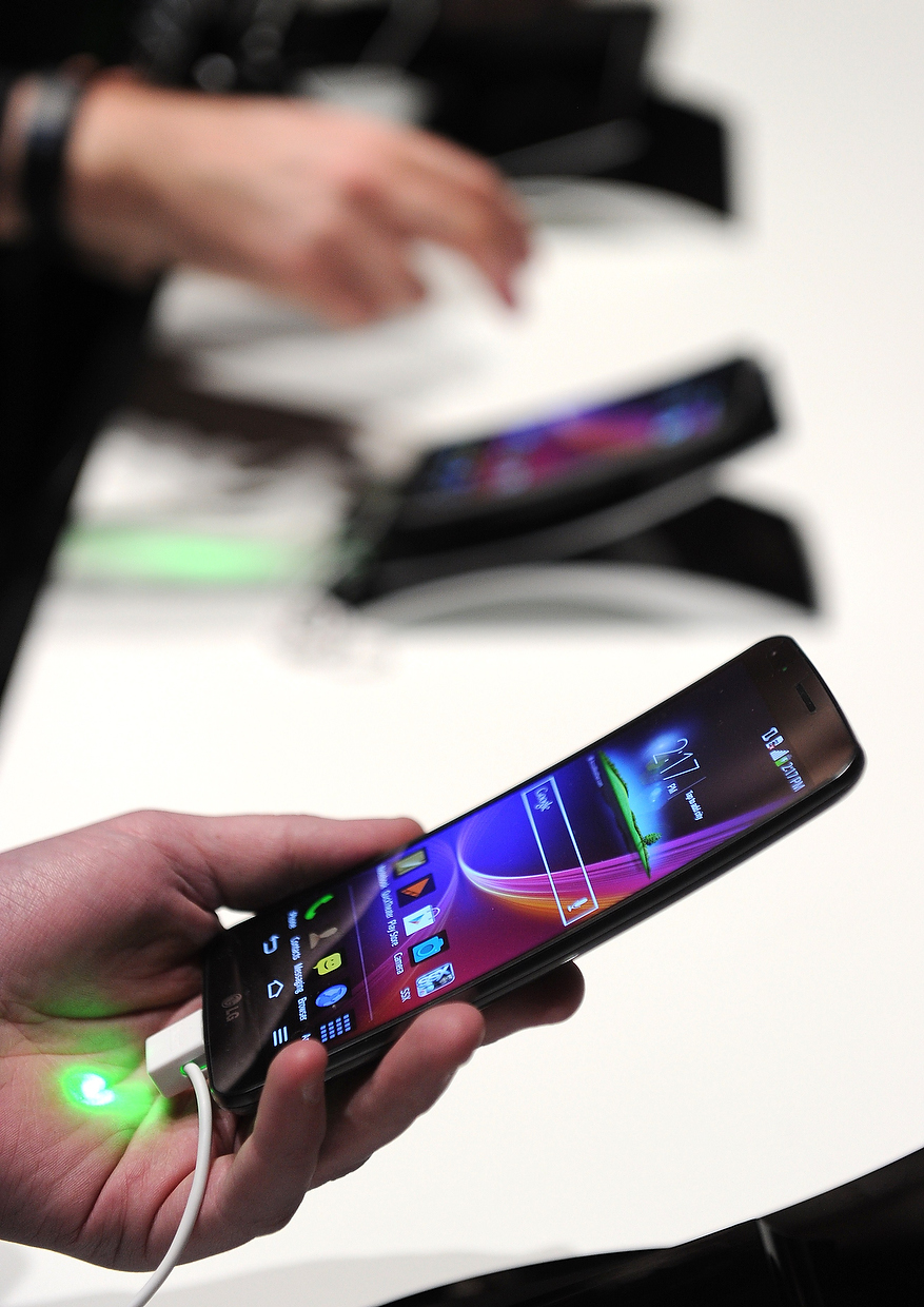 . Attendees look at LG\'s new G Flex curved screen smartphone, at the LG press conference at the Mandalay Bay Convention Center for the 2014 International CES on January 6, 2014 in Las Vegas, Nevada. (ROBYN BECK/AFP/Getty Images)