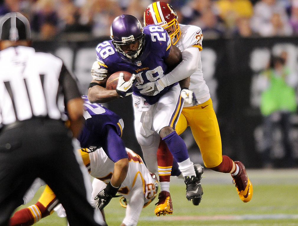 . Minnesota running back Adrian Peterson gets wrapped up from behind by Washington strong safety Reed Doughty in the third quarter. (Pioneer Press: John Autey)