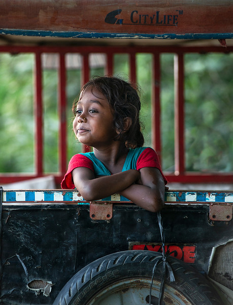 A cute little girl playing inside an old rickshaw.   Chitwan national park, Nepal, 2019.