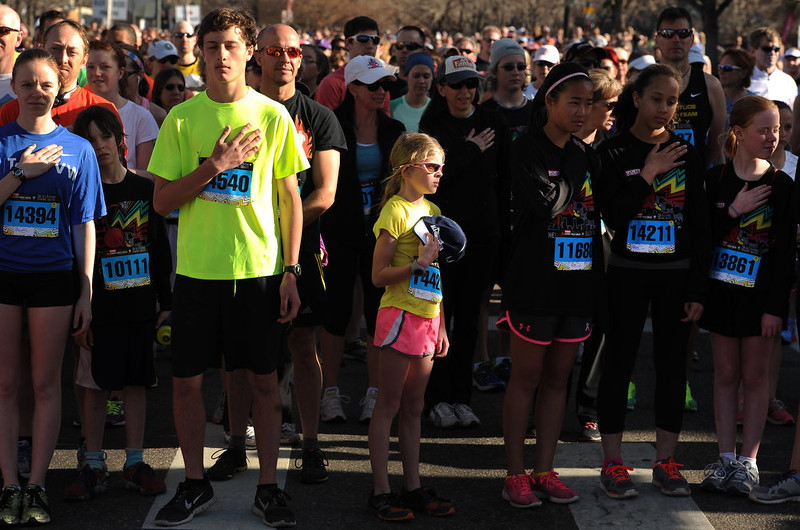 . Alayna Szuch, 9, holds her hat and hand to her heart at the beginning of the 5K race during the singing of the national anthem. The 31st annual Cherry Creek Sneak had all sorts of distances for this year\'s race.  The Sneak, as it is affectionately named, had a 10 mile, 5 mile, 3.1 mile or 5K, a 1.5 mile Denver\'s 7 Sprint, and a kid\'s fun run for thousands of competitors, runners and walkers that turned out in the Cherry Creek neighborhood of Denver, CO on April 28, 2013.  The race is always held the last Sunday in April. This year participants cheered the national anthem and observed a moment of silence for victims of the Boston Marathon bombing at the start of each race. (Photo by Helen H. Richardson/The Denver Post)