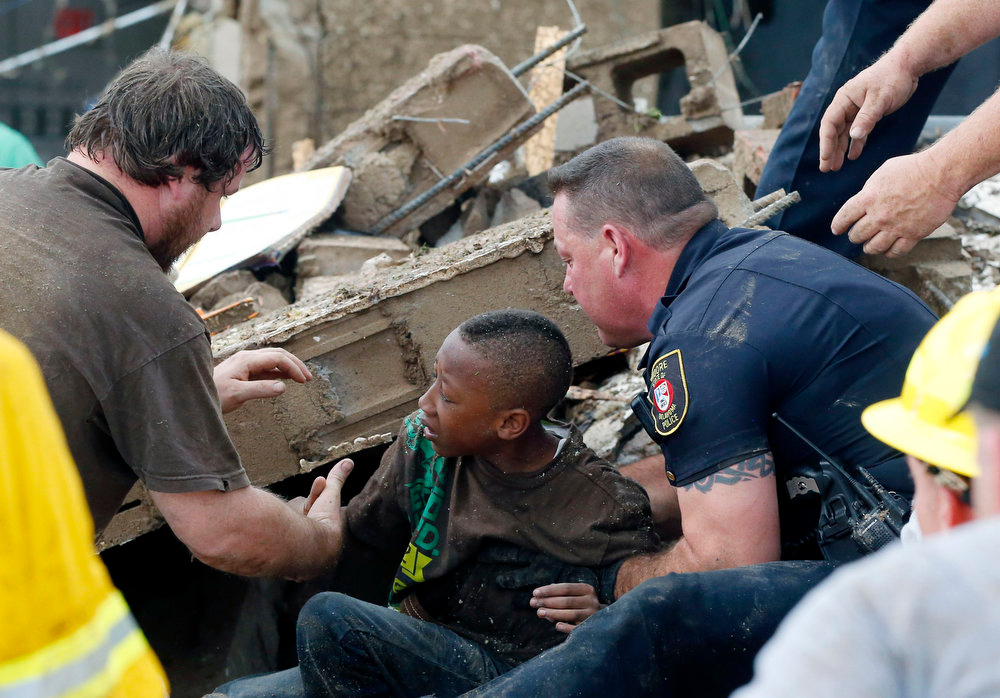 . A boy is pulled from beneath a collapsed wall at the Plaza Towers Elementary School following a tornado in Moore, Okla., Monday, May 20, 2013. A tornado as much as a mile (1.6 kilometers) wide with winds up to 200 mph (320 kph) roared through the Oklahoma City suburbs Monday, flattening entire neighborhoods, setting buildings on fire and landing a direct blow on an elementary school. (AP Photo/ Sue Ogrocki)