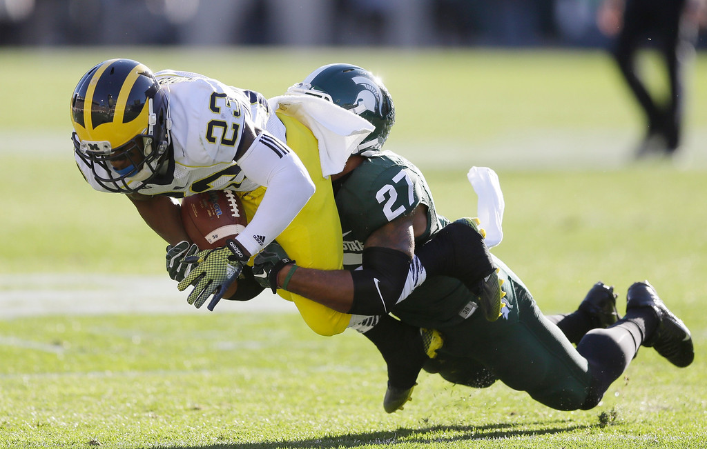 . Michigan wide receiver Dennis Norfleet (23) is hit by Michigan State safety Kurtis Drummond (27) during the first half of an NCAA college football game in East Lansing, Mich., Saturday, Oct. 25, 2014. (AP Photo/Carlos Osorio)