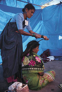 Former Devadasis  are now organized and rebelling against the Devadasi system. A volunteer  from the activist  organization, Myrada cuts the ritual dreadlocks  of a Devadasi child. When the dreadlocks  are cut, it's believed that  the power of the goddess  is broken. Saundatti, Karnataka, India.