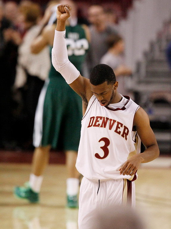 . Denver guard Jalen Love, front, raises his arm in the air as Ohio forward Reggie Keely, back, reacts after Denver\'s 61-57 victory in a first-round game NIT college basketball game in Denver on Tuesday, March 19, 2013. (AP Photo/David Zalubowski)