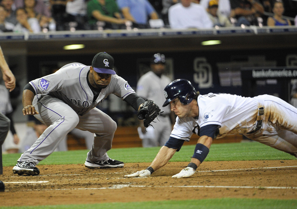 . SAN DIEGO, CA - SEPTEMBER 6:  Chris Denorfia #13 of the San Diego Padres scores ahead of the tag by Juan Nicasio #12 of the Colorado Rockies during the sixth inning of a baseball game at Petco Park on September 6, 2013 in San Diego, California.  (Photo by Denis Poroy/Getty Images)