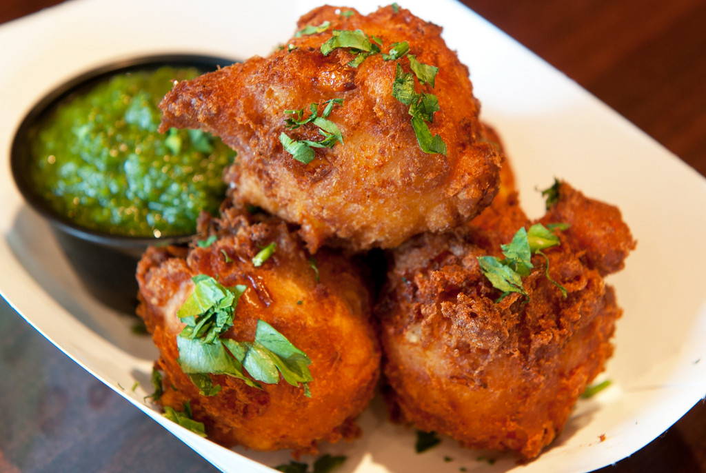. Blue Cheese & Corn Fritz � Four deep-fried corn fritters stuffed with crumbled blue cheese and served with a fresh herb chimichurri. At The Blue Barn* (New Food Vendor for 2014), west of the Skyride at West End Market. (Courtesy of Minnesota State Fair)