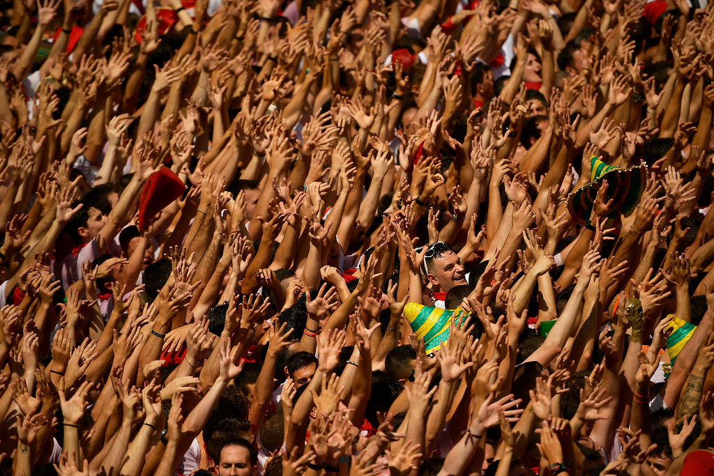 . Revellers hold their arms up during the launch of the \'Chupinazo\' rocket, to celebrate the official opening of the 2018 San Fermin fiestas with daily bull runs, bullfights, music and dancing in Pamplona, Spain, Friday July 6, 2018. (AP Photo/Alvaro Barrientos)
