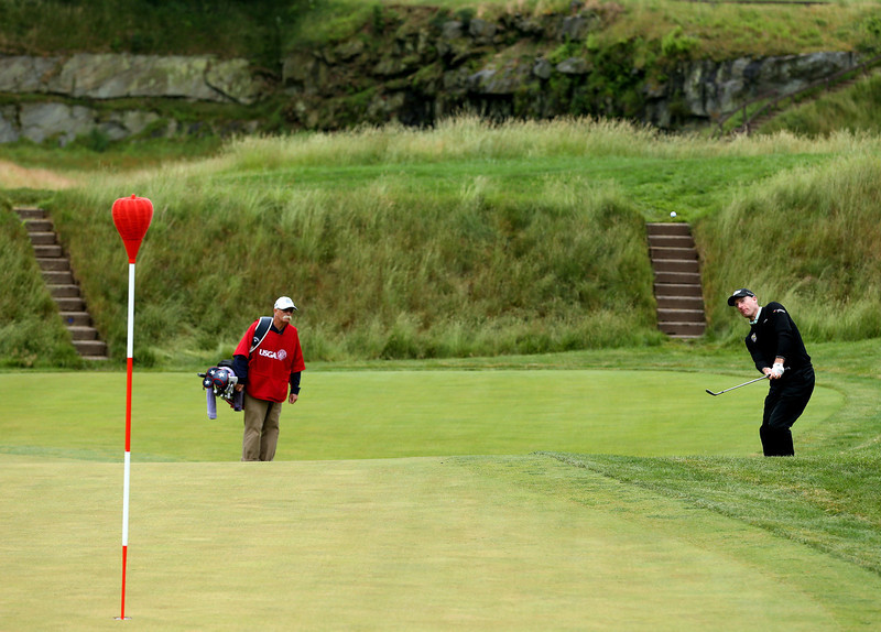. Jim Furyk of the United States chips to the 17th green as caddie Mike \'Fluff\' Cowan looks on during a continuation of Round One of the 113th U.S. Open at Merion Golf Club on June 14, 2013 in Ardmore, Pennsylvania.  (Photo by Andrew Redington/Getty Images)