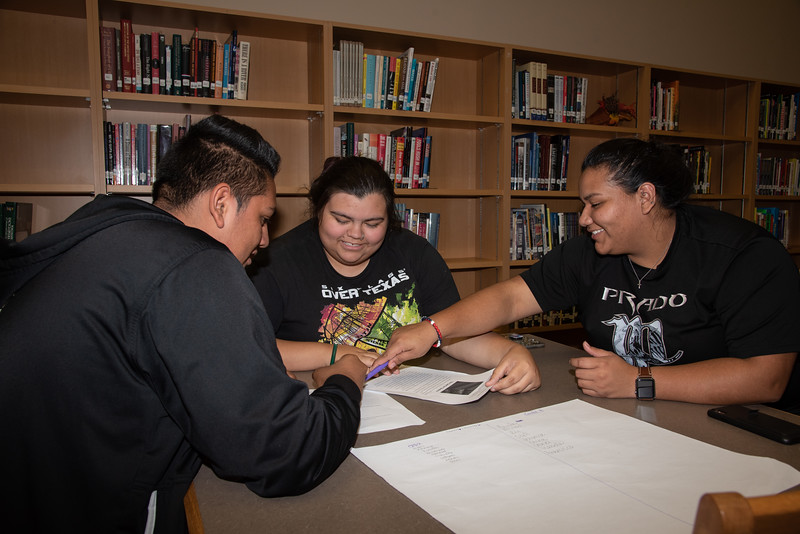 Kendra Baez (middle) and Brianda Ramirez with a West Oso High School student at the Spanish event at the library.