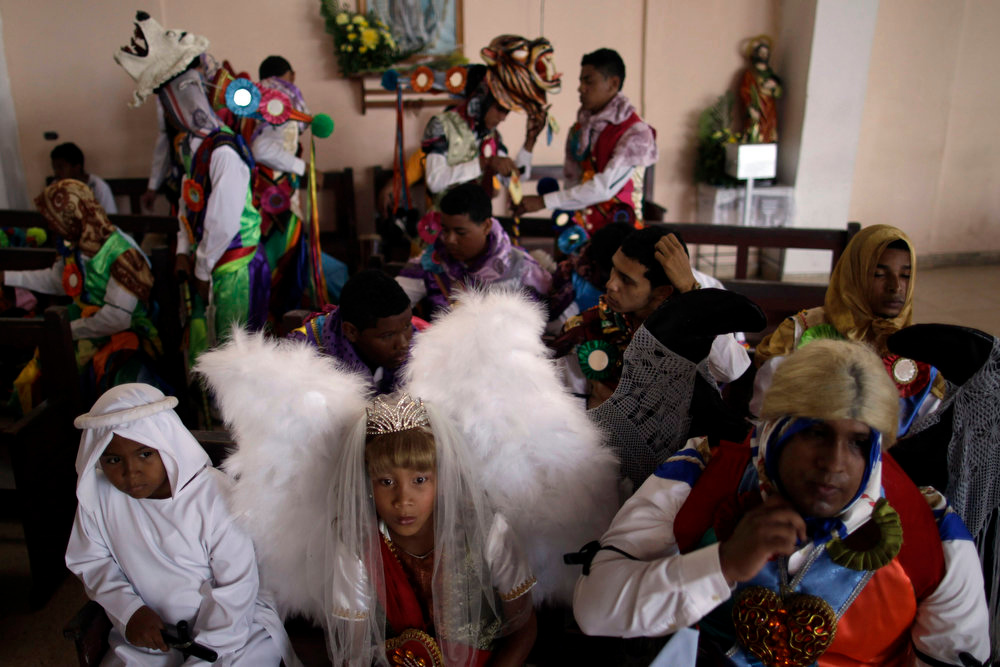 ". A girl dressed as an angel (C) sits between youths dressed as a devil (R) and a soul as they listen to the annual Corpus Christi service in La Chorrera on the outskirts of Panama City May 30, 2013. During the celebration, people dressed as colorful devils, angels and souls, dance the ""El Baile del Gran Diablo\"" (the Great Devil Dance), representing the struggle between good and evil, in a mixture of Spanish and indigenous traditions. REUTERS/Carlos Jasso"