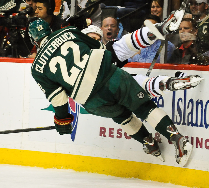 . Minnesota right wing Cal Clutterbuck slams Chicago defenseman Brent Seabrook into the boards in the the first period.  (Pioneer Press: Ben Garvin)