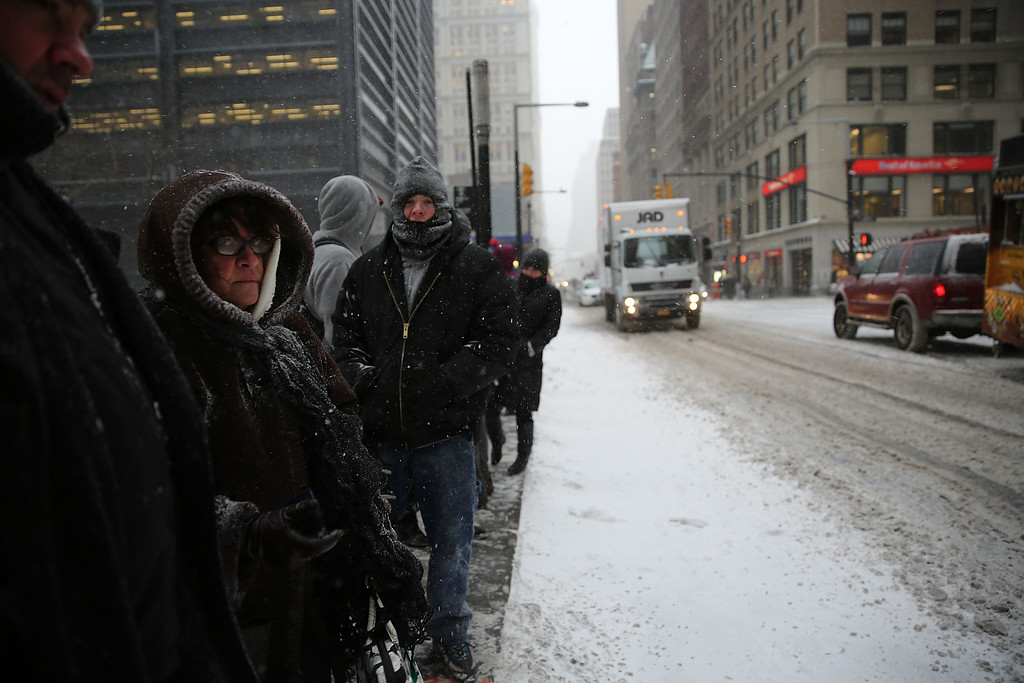 . NEW YORK, NY - JANUARY 26:  People wait at a bus stop, some for over two hours, during heavy snow in the financial district of Manhattan on January 26, 2015 in New York City. New York, and much of the Northeast, is bracing for a major winter storm which is expected to bring blizzard conditions and 18 to 24 inches of snow to the area. New York Mayor Bill de Blasio has announced that only emergency vehicles will be allowed on area roads after 11pm.  (Photo by Spencer Platt/Getty Images)