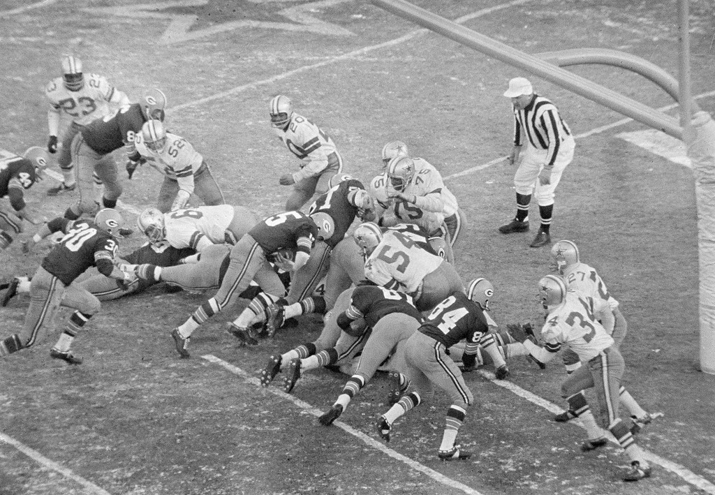 . With seconds remaining, quarterback Bart Starr (15), Green Bay Packers, bulls way behind the Packers\' play leader - the center - and key blocker Jerry Kramer (64), who is delivering key block to Dallas\' tackle Jethro Pugh (75), Dec. 31, 1967. Starr gave Green Bay a 21-17 NFL victory for its third year in a row.  (AP Photo)