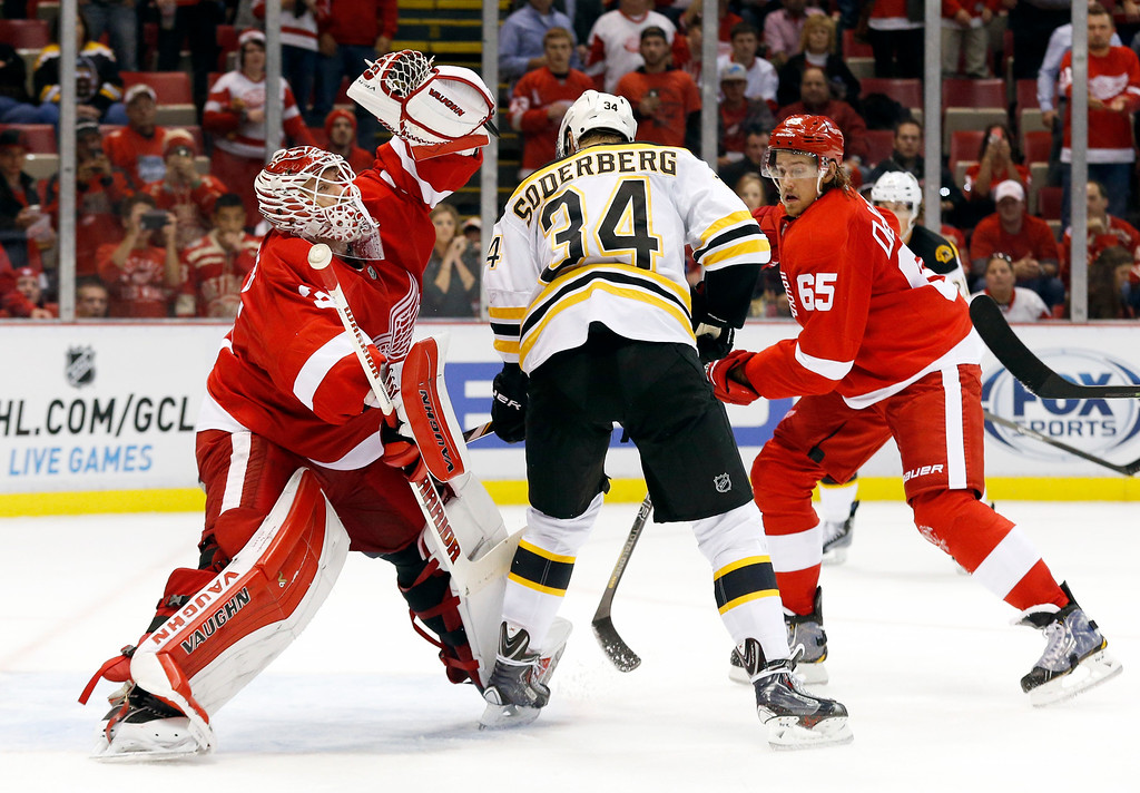 . Detroit Red Wings goalie Jimmy Howard (35) stops a shot as Boston Bruins center Carl Soderberg (34) is defended by defenseman Danny DeKeyser (65) in the third period of an NHL hockey game in Detroit Thursday, Oct. 9, 2014. Detroit won 2-1. (AP Photo/Paul Sancya)