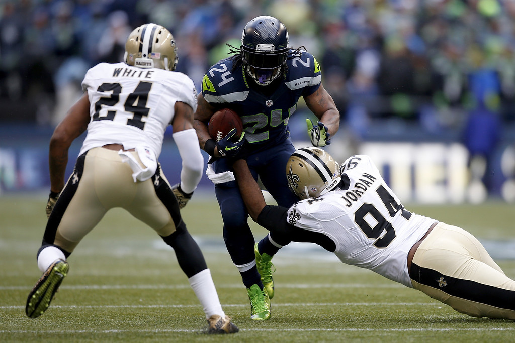 . SEATTLE, WA - JANUARY 11:  Running back Marshawn Lynch #24 of the Seattle Seahawks runs the ball against cornerback Corey White #24 and defensive end Cameron Jordan #94 of the New Orleans Saints in the first quarter during the NFC Divisional Playoff Game at CenturyLink Field on January 11, 2014 in Seattle, Washington.  (Photo by Otto Greule Jr/Getty Images)