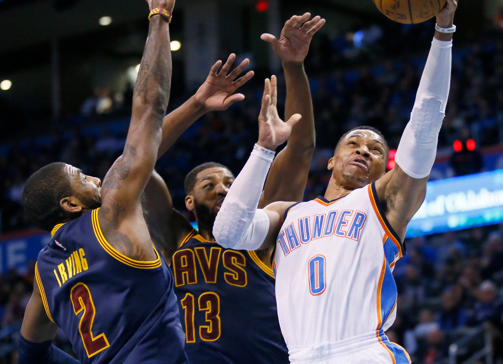 . Oklahoma City Thunder guard Russell Westbrook (0) shoots in front of Cleveland Cavaliers guard Kyrie Irving (2) and center Tristan Thompson (13) during the third quarter of an NBA basketball game in Oklahoma City, Thursday, Feb. 9, 2017. Oklahoma City won 118-109. (AP Photo/Sue Ogrocki)