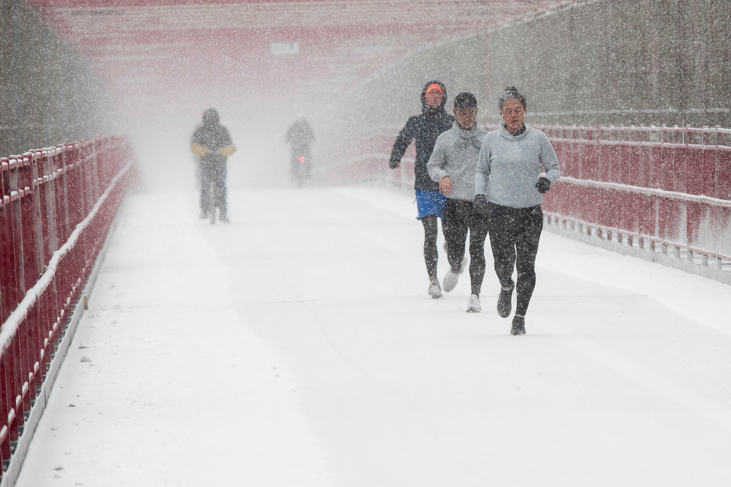 . People run in the snow across the Williamsburg bridge, Saturday, Jan. 7, 2017, in New York.  The Weather Service issued a winter weather advisory for New York City and the northern suburbs. Snow began falling from New York City and points east at mid-morning Saturday. (AP Photo/Mary Altaffer)