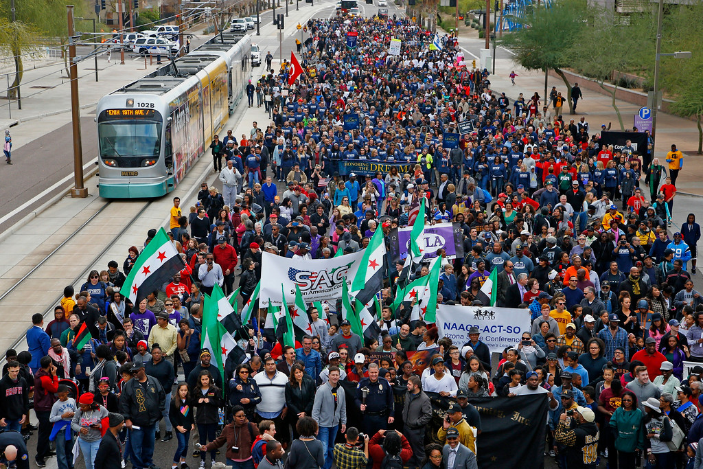 . Participants take to the streets for a Martin Luther King Jr. Day march celebrating the life of the civil rights leader Monday, Jan. 16, 2017, in Phoenix. (AP Photo/Ross D. Franklin)