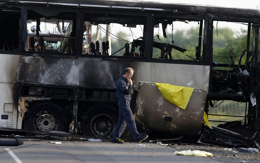 . An official walks past the remains of a tour bus that was struck by a FedEx truck on Interstate 5 Thursday in Orland, Calif., Friday, April 11, 2014. At least ten people were killed and dozens injured in the fiery crash between the truck and a bus carrying high school students on a visit to a Northern California College. (AP Photo/Jeff Chiu)