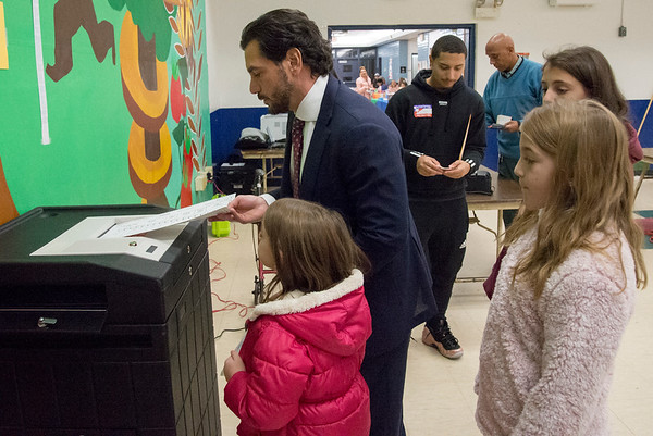 11/05/19 Wesley Bunnell | StaffrrState Senator Gennaro Bizzarro casts his ballots surrounded by his daughters at Slade Middle School on Tuesday evening.