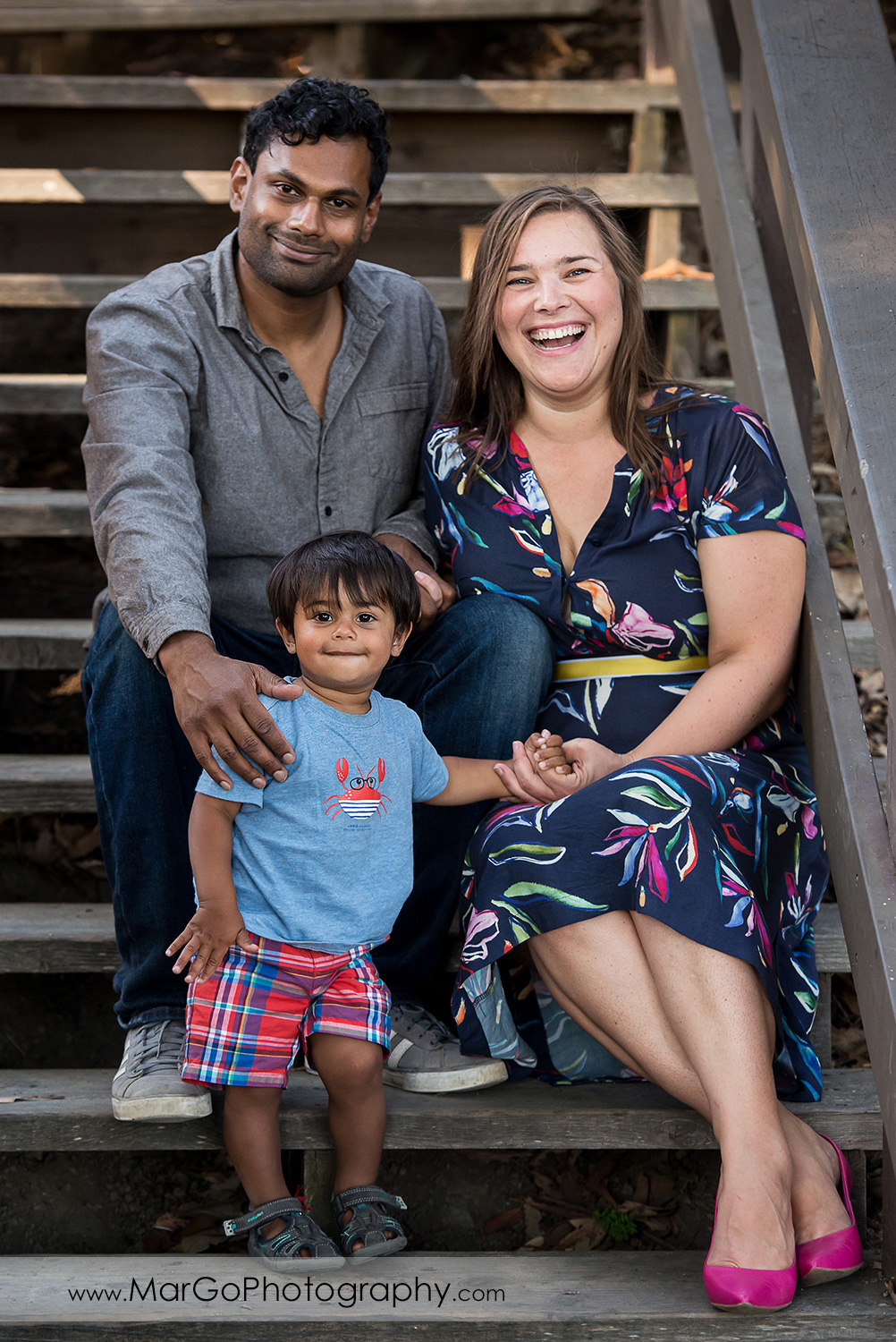 family portrait of woman in blue dress with pink flowers, man in grey shirt and little boy in blue shirt sitting on the stairs at Richmond Keller Beach