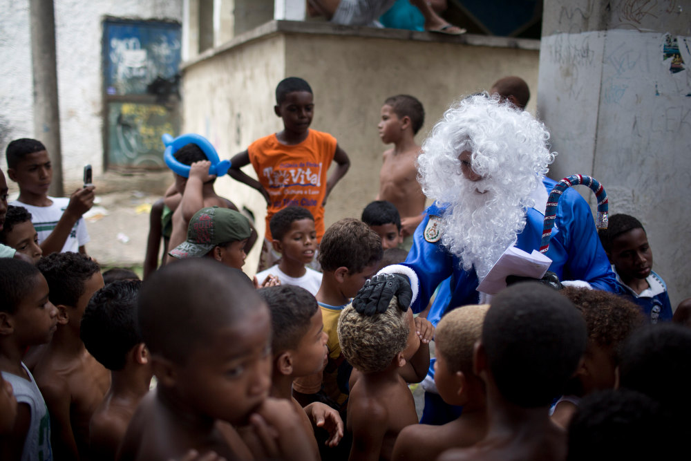. A police officer dressed in a blue Santa Claus costume, with the blue color representing the police, is surrounded by kids after handing out gifts in the Macacos slum in Rio de Janeiro, Brazil, Thursday, Dec. 20, 2012. The Pacifying Police Unit, or UPP, organized for Santa to visit the pacified slum to hand out Christmas gifts to young residents. (AP Photo/Felipe Dana)